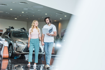 young couple with catalog buying car at dealership salon