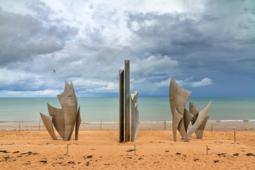 Beautiful view of WWII monument Les Braves, on the center of Omaha Beach in Normandy, France, with clouds in summer