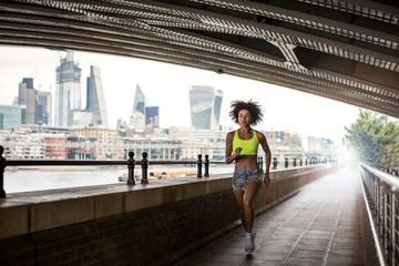 Young female athlete running on footbridge in city