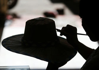 Chhun Maleang, 26, paints an Apsara dancer on a hat at her shop in Phnom Penh