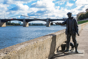The monument to fisherman and the cat on the embankment of the river Volga in Tver, Russia. Picturesque clouds in the sky. Road bridge on the horizon. Summer or autumn Sunny day.