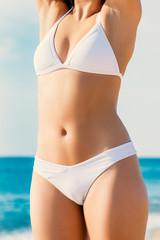 Detail of female body in white bikini outdoors.