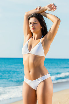 Young attractive woman in white bikini showing toned body outdoors.