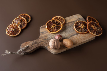 Nuts, oranges on a wooden brown background