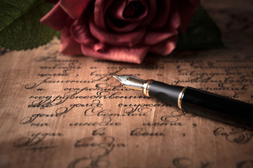 fountain pen on letter with text and red rose