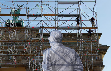 A steel scaffolding is erected with giant figures displaying former East German border soldiers in front of the Brandenburg Gate for the upcoming celebrations to mark the anniversary of Germany's unification in Berlin