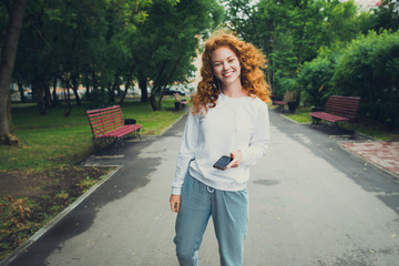 happy girl walking in park, holding smartphone