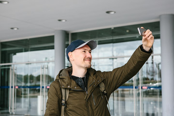 A guy in a baseball cap or a tourist photographs or does selfie on the phone and smiles.