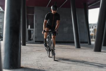 Sportsman riding bike next to modern building inside urban bridge.
