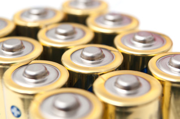 closeup of golden and silver aa alkaline batteries group on white background