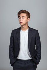 Studio portrait of a young East Asian man looking up