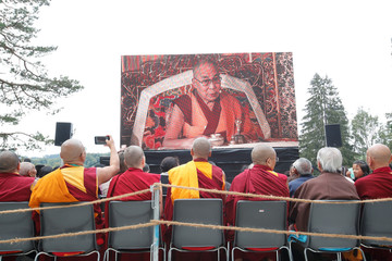 People watch the speech of Tibetan spiritual leader the Dalai Lama on a huge screen during his visit to the Tibet Institute Rikon in Rikon
