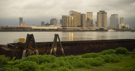 The Mississippi River Flows By The Barges and Buildings New Orleans Waterfront