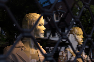 Mannequins behind a security fence.