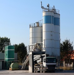 A cement mixer truck is supplied to a concrete silo in a batching plant