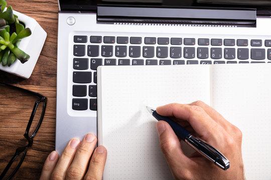 Man Writing On Blank Notepad