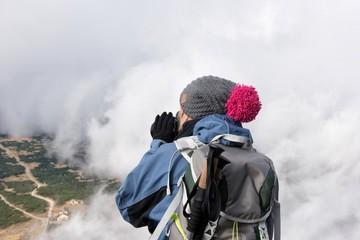 Trekking po górach z aparatem fotograficznym w chmurach.