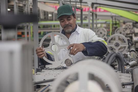 Worker checking label machine