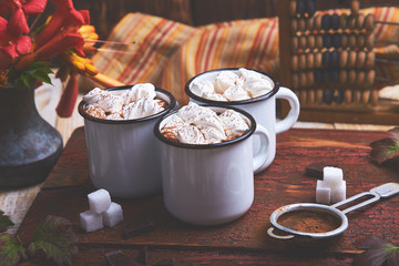 Hot chocolate with marshmallow candies on wooden background.