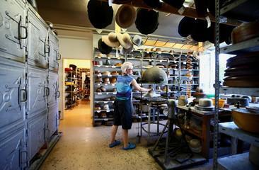 An employee of headwear manufacturer Muehlbauer puts a hat under a steam bell at their workshop in Vienna
