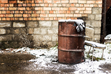 rusty barrel of oil on a background of wet stone walls, snow-covered yard