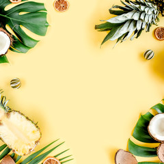 Tropical frame, background with exotic fruits and tropical palm leaves on yellow background with space for text. Flat lay, top view