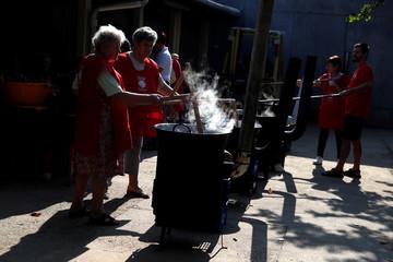 Elderly women cook plum marmalade in Bordany