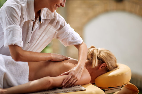 Smiling masseur is massaging a woman at spa close up.