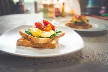 Breakfast sandwich with egg, watercress and tomato on the table, healthy food