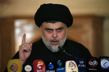 Iraqi Shi'ite radical leader Muqtada al-Sadr delivers a sermon to worshippers during Friday prayers at the Kufa mosque near Najaf