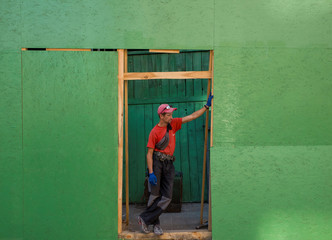 A worker is seen at the entrance of a reconstructed shop in central Kiev