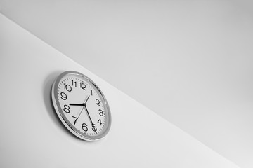 Clock on the white wall, management concept, deadline, passing time, time running out, black and whie tone