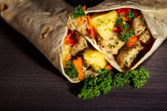 Chicken and pineapple tortilla wrap on dark background