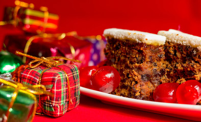 Fruitcake and small gifts depicting Christmas celebrations on red background