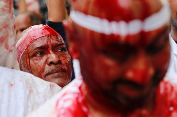 Shi'ite Muslim men flagellate themselves during a Muharram procession to mark Ashura, in Mumbai