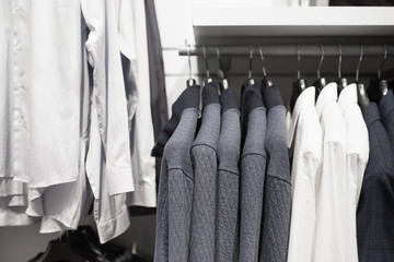 Shop men's clothing, white shirts and jackets on hangers.