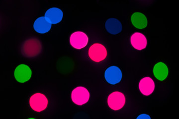 magic lights of blurred garlands bright and festive on a dark background