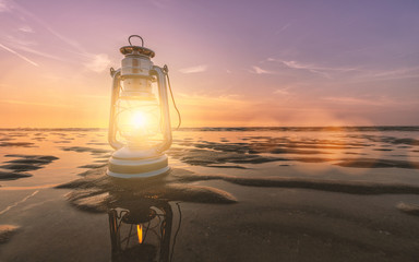 vintage lantern at the beach on a summer sunset, romantic concept image