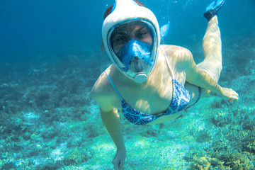 Snorkeling girl in bikini and full-face snorkeling mask in coral reef. Snorkel in coral reef of tropical sea.
