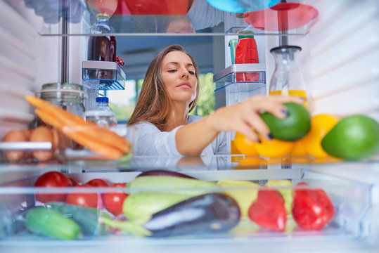Woman standing in front of opened fridge and taking avocado. Fridge full of groceries.