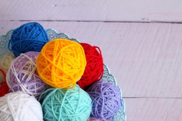 Colorful yarn balls for knitting isolated on a pink background.