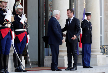 French President Emmanuel Macron welcomes Palestinian President Mahmoud Abbas as he arrives for a meeting at the Elysee Palace in Paris