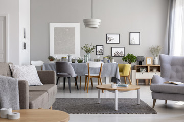 Real photo of a modern living room interior with a dining table and graphics on a wall