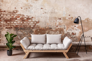 Grey wooden sofa between plant and black lamp in living room interior with red brick wall. Real...