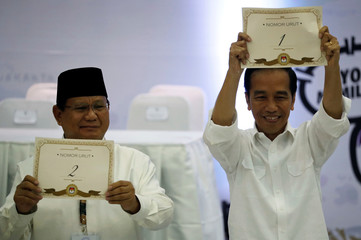 Indonesian President Joko Widodo and his opponent in next year's presidential elections Prabowo Subianto, a retired special forces commander, hold their ballot numbers during a ceremony at the election commission headquarters in Jakarta