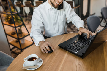 Happy businessman is speaking phone and printing on the laptop