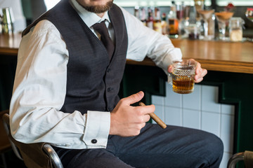 Man in waistcoat sits from the bar with whiskey and cigar. No face closeup
