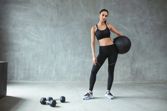 Sports Woman In Black Sportswear Training With Fitness Ball