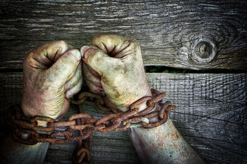 Strong dirty male hands clenched into fists chained with rusty chain on wooden boards background
