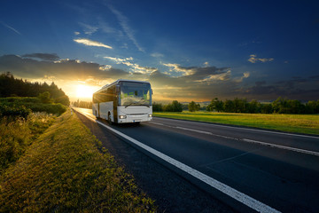 Fotobehang - White bus arriving on the asphalt road in rural landscape in the rays of the sunset